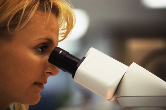 womean looking in microscope